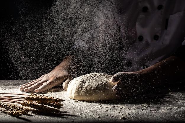 White flour flying into air as pastry chef in white suit slams ball dough on white powder Premium Photo