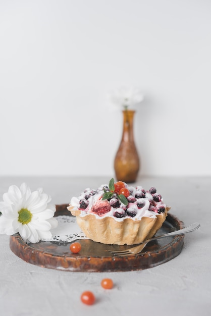White flower and delicious mini tarts with fresh berries on wooden serving tray Free Photo