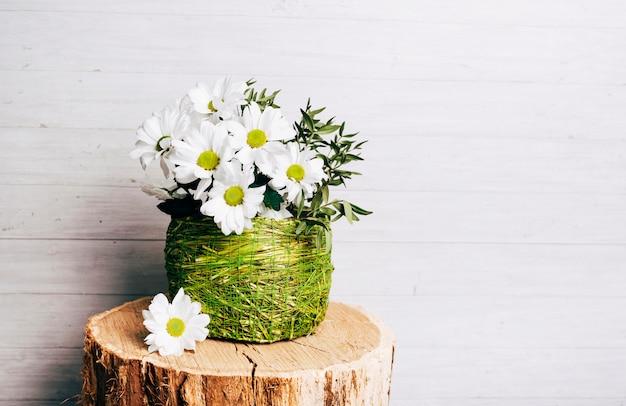 White flower vase on tree stump against wooden background Free Photo