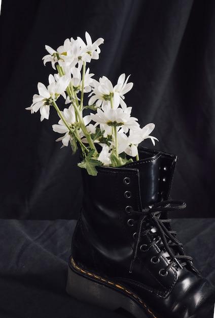 White flowers in dark boot Free Photo