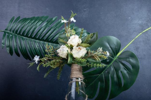 어두운 벽에 세라믹 꽃병에 흰색 꽃입니다. 무료 사진