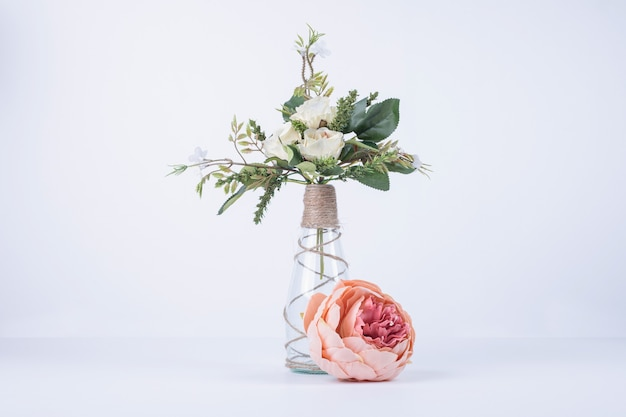 Белые цветы в стеклянной вазе на белом с одной розой. Бесплатные Фотографии