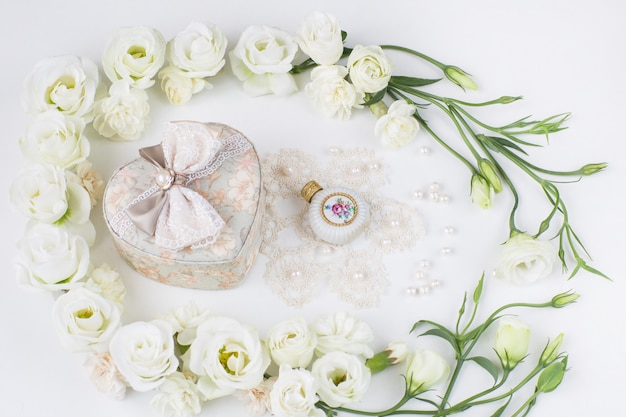 White flowers lined with a heart-shaped jewelry box, perfume bottle, pearls and lace Premium Photo