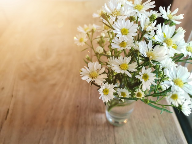 White flowers in metal pot on the wooden table Premium Photo