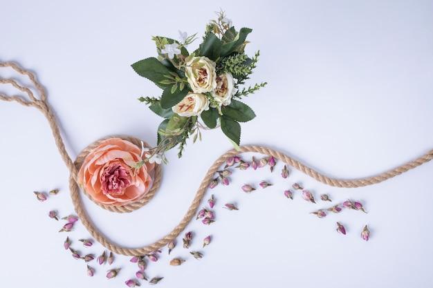 白い花、一本のバラ、白いバラにロープと花びら。 無料写真