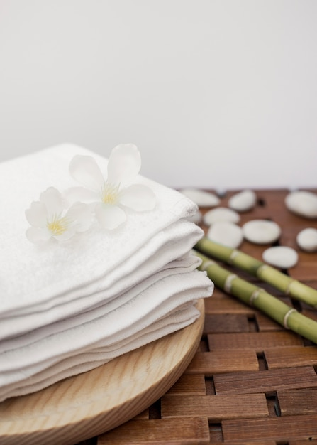 White flowers and stacked towels on wooden tray Free Photo