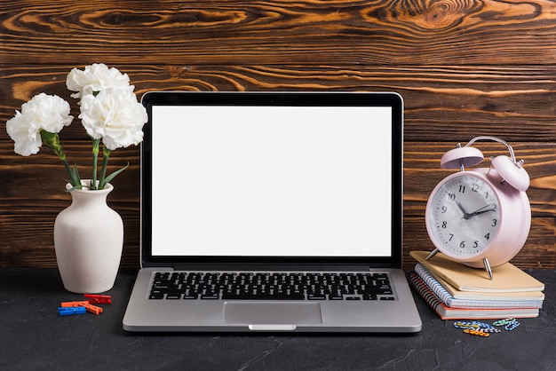 White flowers in the vase; laptop and alarm clock on notebooks against wooden backdrop Free Photo
