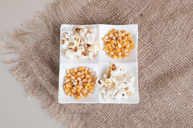 Popcorn soffici bianchi in una tazza di ceramica su cemento. Foto Gratuite