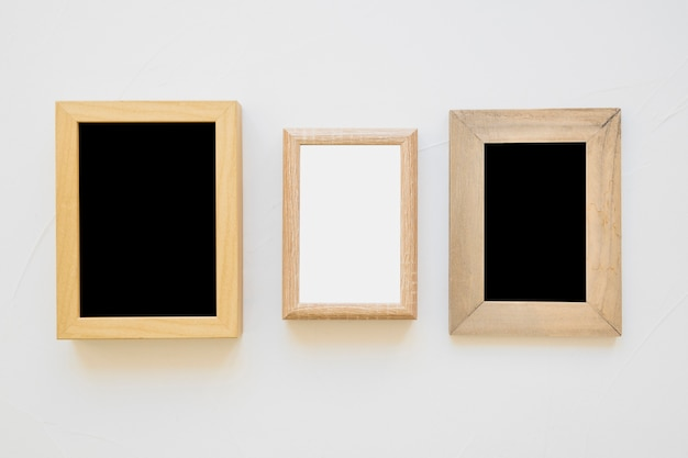 White frame between the black frames on wall Free Photo
