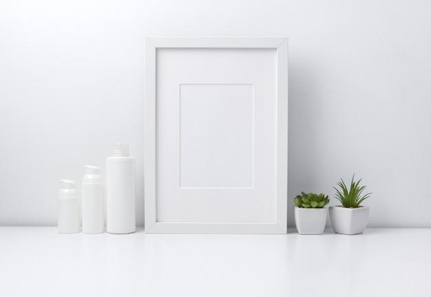 책 선반 또는 책상에 흰색 프레임, 식물 및 화장품 병 용기. 프리미엄 사진
