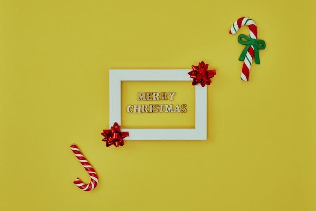 Белая рамка с елочными украшениями и надписью merry christmas на желтом фоне Premium Фотографии