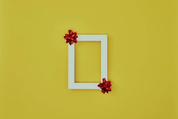 Белая рамка с елочными украшениями на желтом фоне Premium Фотографии