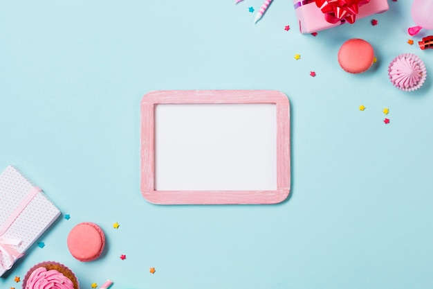 White frame with pink wooden frame with party muffins; aalaw; macaroons and gift boxes on blue backdrop Free Photo