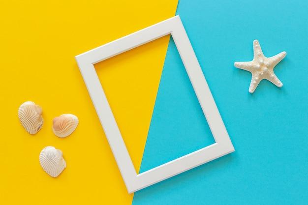 White frame with starfish on blue, yellow background and seashells. Premium Photo