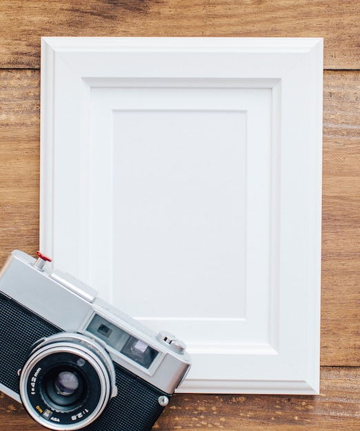White frame on wooden background with old camera Free Photo