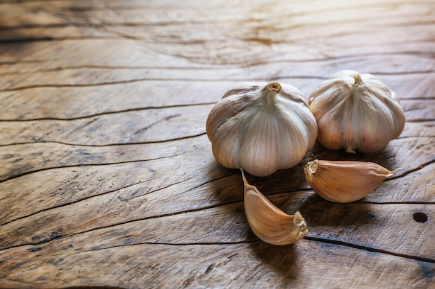 White garlic placed on a dark brown wood floor. Free Photo