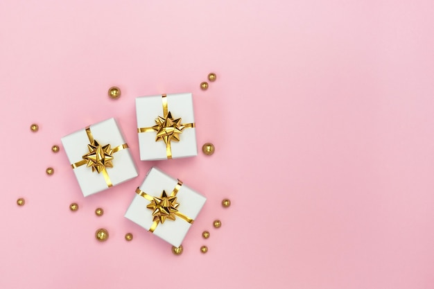 Белые подарочные коробки с золотыми бантами и золотыми украшениями на пастельно-розовом фоне. минималистичная праздничная открытка. плоская планировка, вид сверху, копия пространства. Premium Фотографии