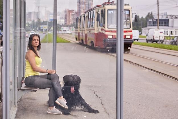 백인 소녀와 그녀의 흑인 브리아 드는 트램을 타고 대중 교통 정류장에 앉아 있습니다. 프리미엄 사진