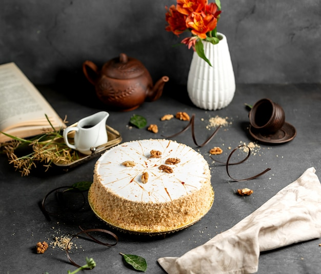 White glazed cake decorated with cake crumbles and walnuts Free Photo