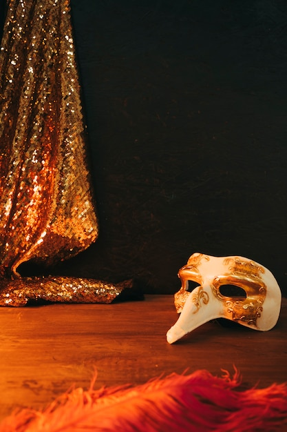White and golden carnival mask with feather and sequins textile against black background Free Photo