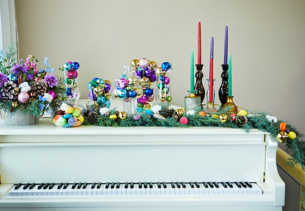 White grand piano decorated in new year's style, christmas tree, christmas toys and balls, candles and macarons Premium Photo