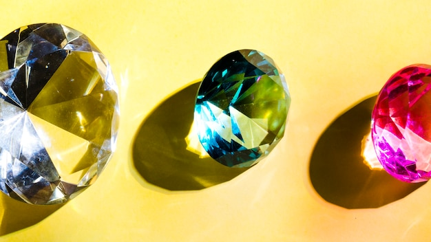White; green and pink crystal diamond on yellow background Free Photo