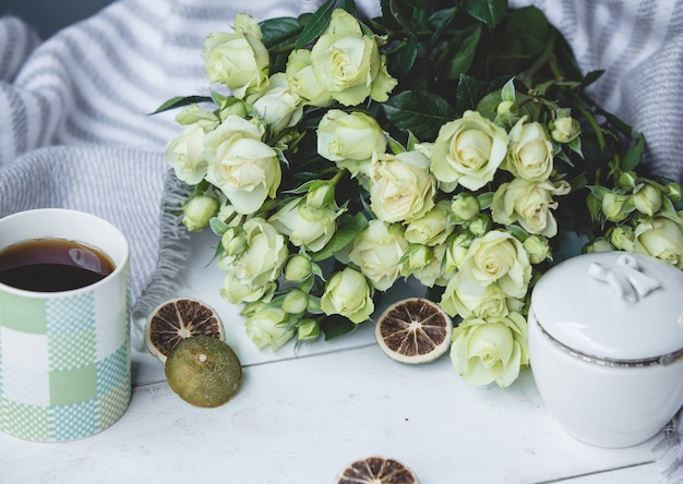 White green roses and a cup of hot tea Free Photo