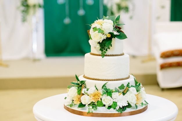 White and green wedding cake with flowers at reception Premium Photo