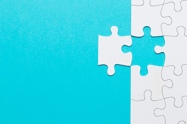 White grid puzzle with missing puzzle piece on blue backdrop Free Photo