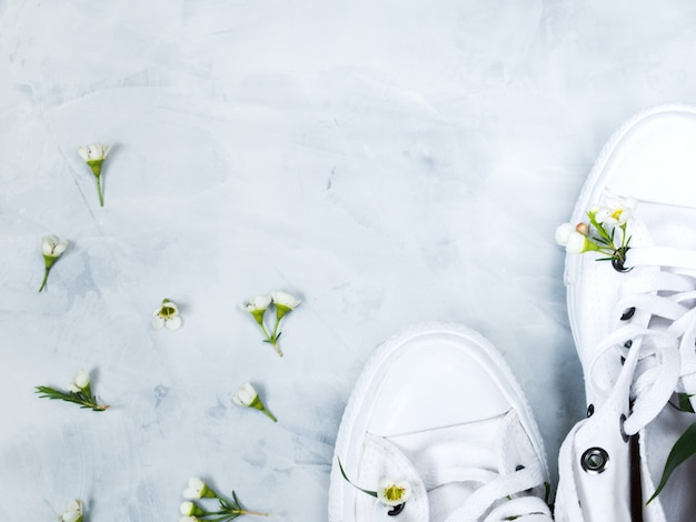 White gumshoes with fresh flowers on grey background Premium Photo