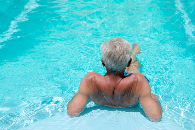 青い水のプールで夏休みを楽しんでいる白い髪の男 Premium写真