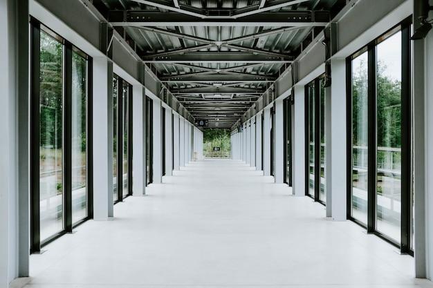 ガラスのドアとモダンな建物の金属天井の白い廊下 無料写真