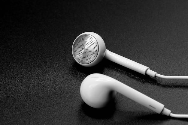 White headphones on black texture with shadow Premium Photo