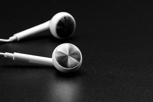 White headphones on black texture with shadow Premium Photo