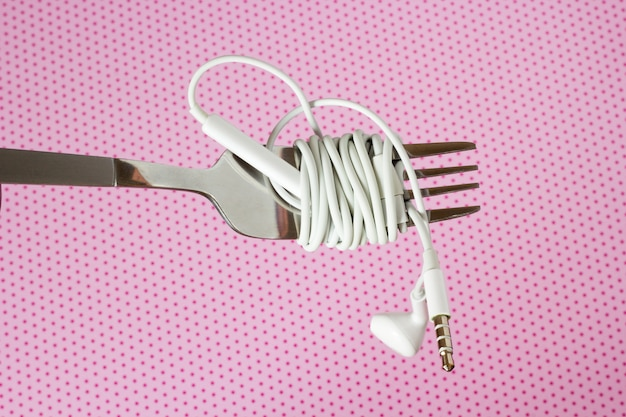 White headphones and fork on a pink background with polka dotsd, close-up Premium Photo