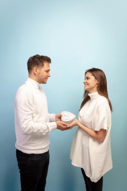 白い心。青いスタジオの壁に恋をしている美しいカップル 無料写真