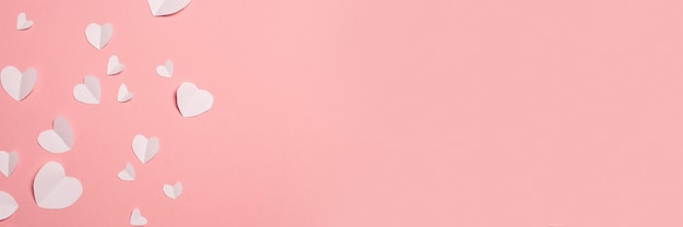 White hearts cut from paper on a pink background. composition of valentine's day. banner. flat lay, top view. Premium Photo