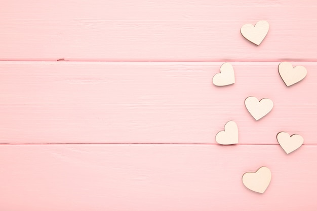 White hearts on a pink background. wooden hearts Premium Photo