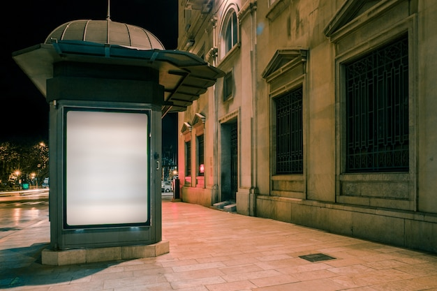 Tabellone per le affissioni in bianco illuminato bianco sul sentiero per pedoni alla notte Foto Gratuite
