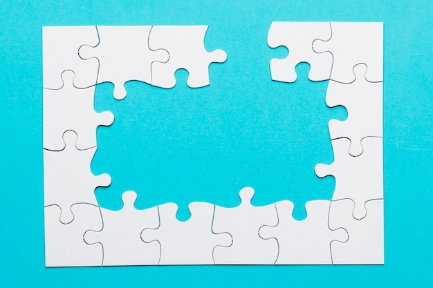 White incomplete white jigsaw puzzle over blue backdrop Free Photo
