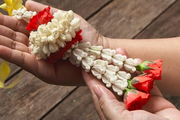 White jasmine garland on wood background, fresh thai style bouquet on the woman's hand Premium Photo