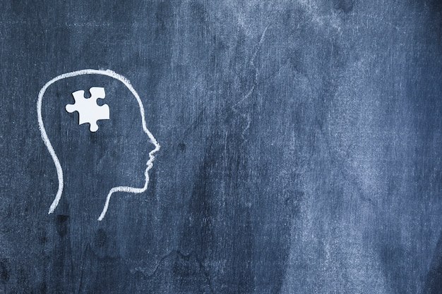 White jigsaw piece on drawn face outline with chalk on chalkboard Free Photo