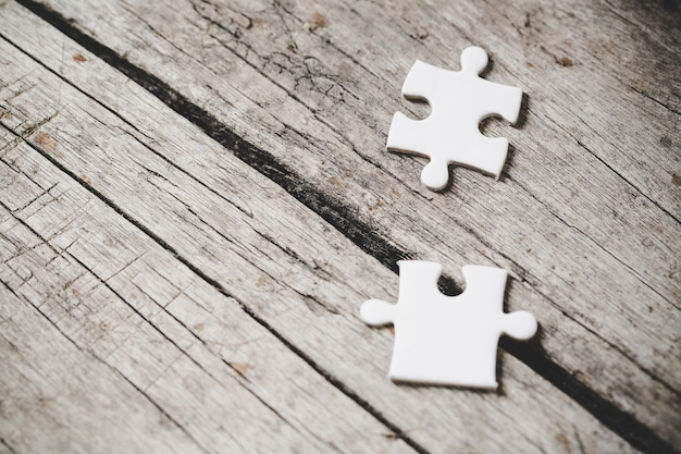 White jigsaw pieces on wood Free Photo