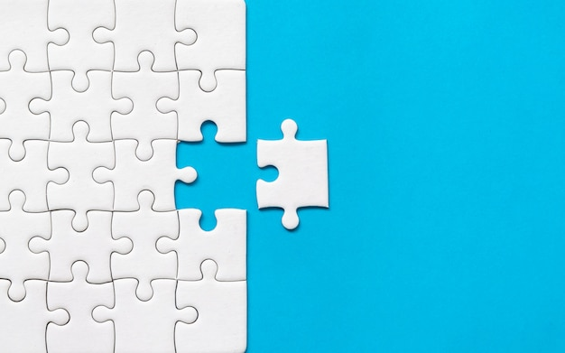 White jigsaw puzzle on blue background. team business success partnership or teamwork. Premium Photo