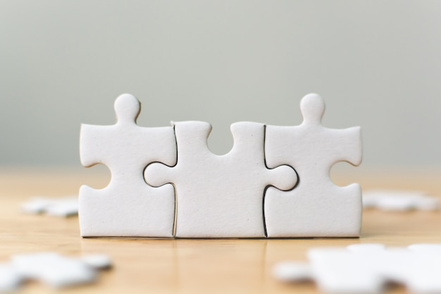 White jigsaw puzzle connecting together. Premium Photo