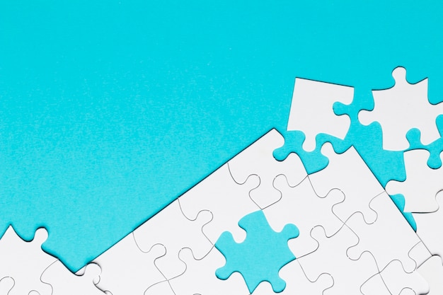 White jigsaw puzzle piece on blue backdrop Free Photo