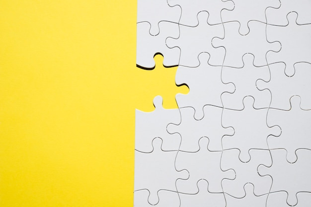 White jigsaw puzzle with one missing piece on yellow backdrop Free Photo