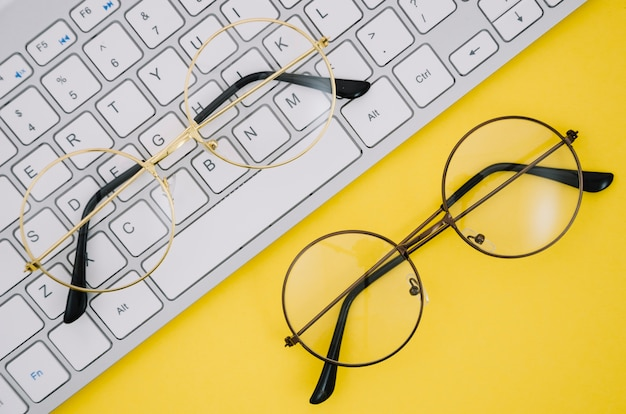 White keyboard and a pairs of glasses on yellow background Free Photo