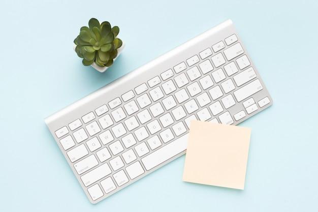 White keyboard next to plant Free Photo