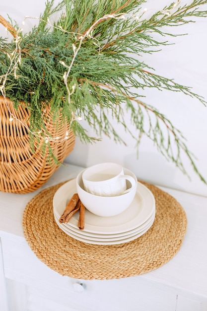 White kitchen set with cinnamon on a saucer and a basket with christmas needles Premium Photo